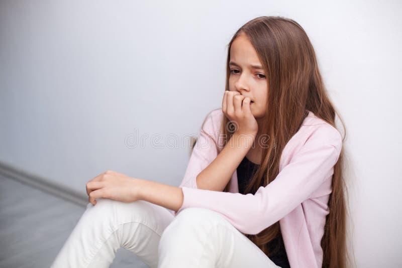 Zmartwiony młody nastolatek dziewczyny obsiadanie na podłoga ścianą zdjęcie royalty free
