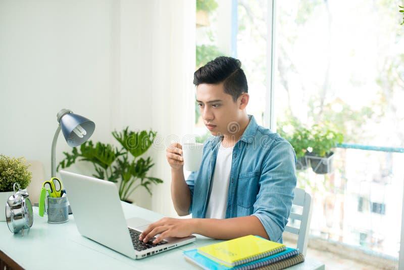 Zmartwiony przedsiębiorcy młody człowiek pracuje przy biurkiem na laptopu patrzeć zdjęcia royalty free