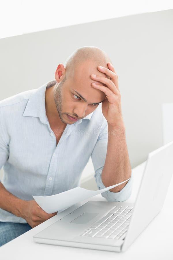 Zmartwiony przypadkowy młody człowiek używa laptop w domu obraz stock