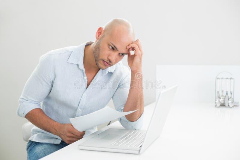 Zmartwiony przypadkowy młody człowiek używa laptop w domu obrazy stock