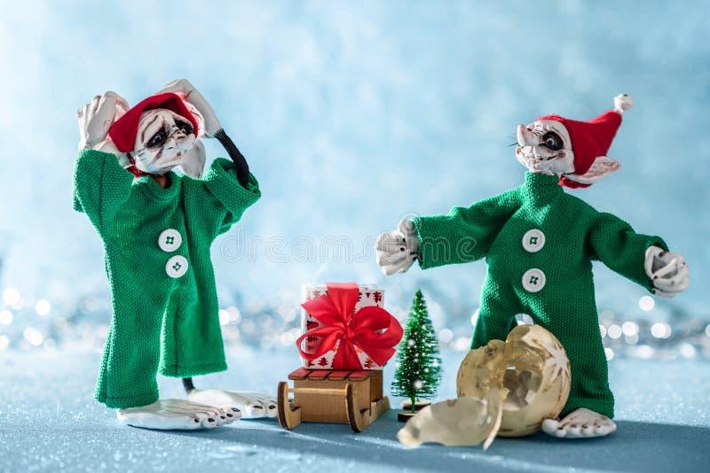 Zmartwiony Santas pomagiera elf Z głową Stoi Obok Innego elfa Który Łamał Bożenarodzeniowego Bauble w rękach Biegunów Północnych  zdjęcie royalty free