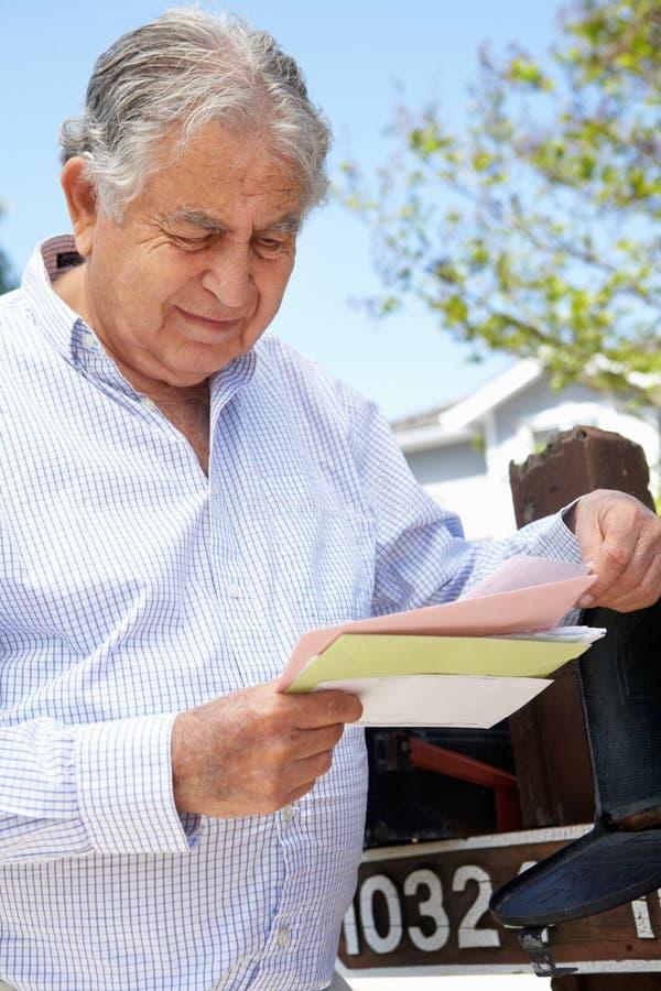 Zmartwiony Starszy Latynoski mężczyzna Sprawdza skrzynkę pocztowa zdjęcie stock