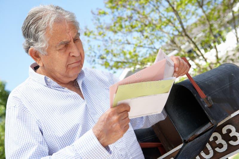 Zmartwiony Starszy Latynoski mężczyzna Sprawdza skrzynkę pocztowa zdjęcia royalty free