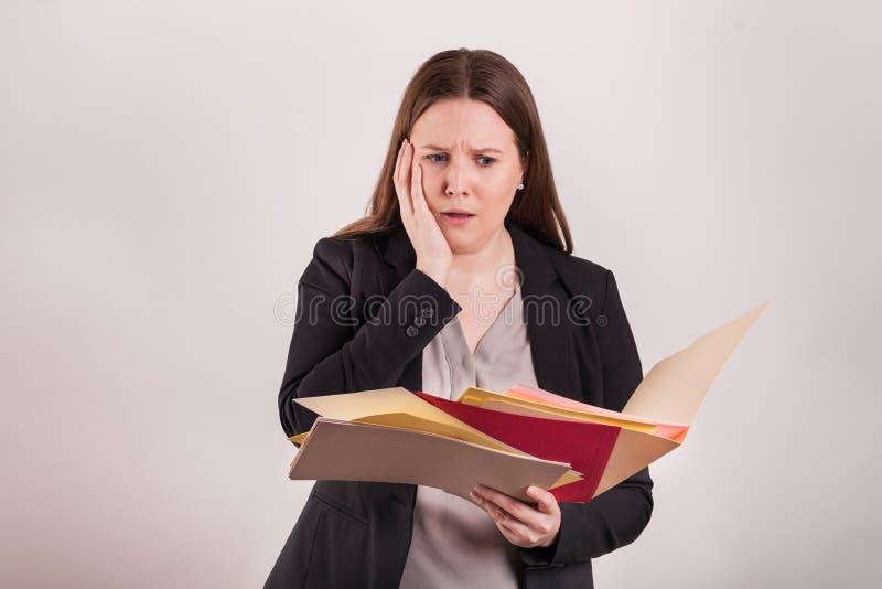 Zmartwiony stresujący wyrażenie na kobiety twarzy mieniu rozpraszał papiery i falcówki zdjęcia royalty free