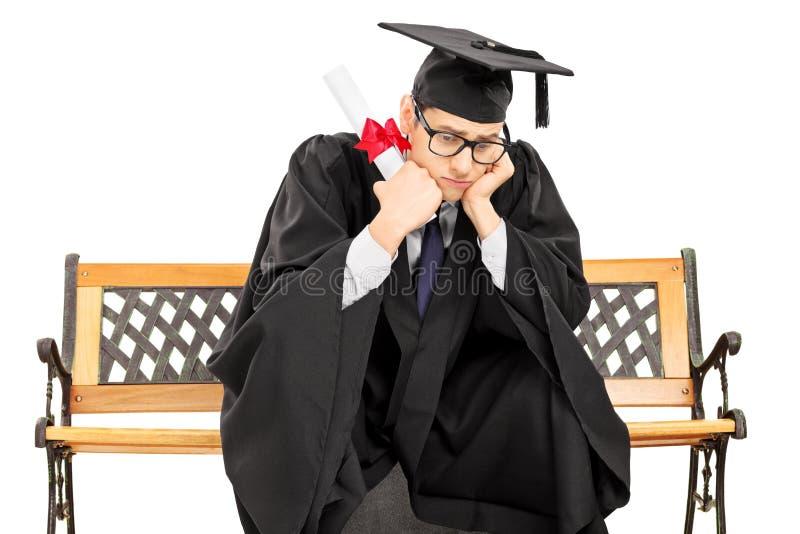 Zmartwiony uczeń w skalowanie todze na ławki mienia dyplomu fotografia stock