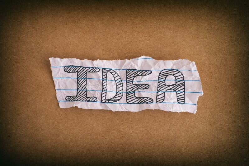 Zmięty kawałek papieru z słowo pomysłem na brązu papieru tle zdjęcia stock