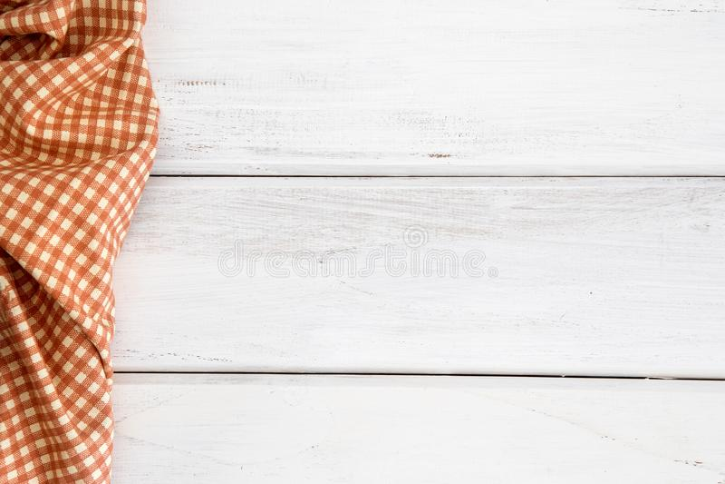 Zmięty pomarańczowy w kratkę tablecloth lub pielucha na pustym bielu wo zdjęcia stock