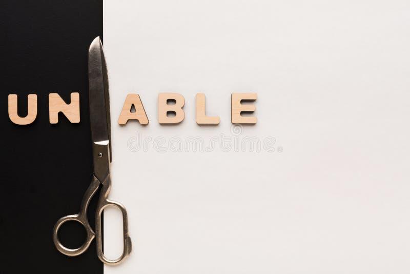 Zmieniający słowo niezdolnego w sprawnie z nożycami zdjęcie stock