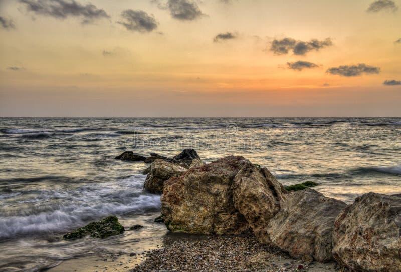 Zmierzch drży denne fala z skalistym seashore, Israel zdjęcia stock
