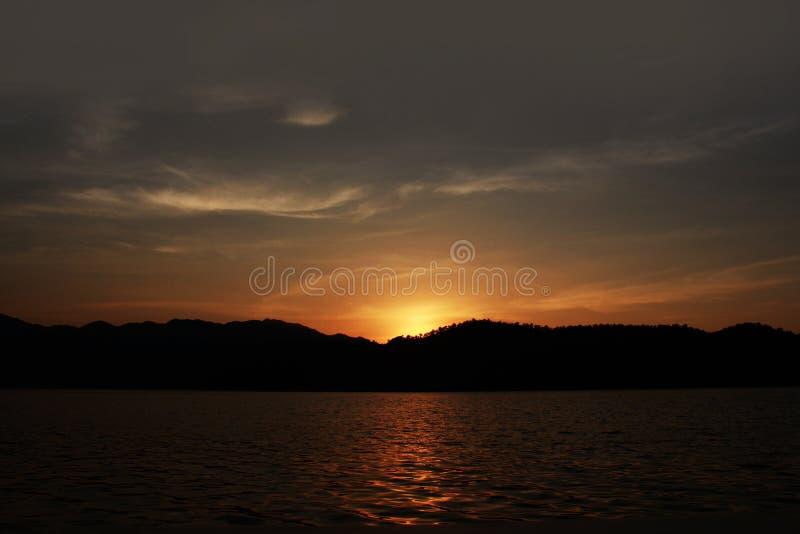 Zmierzch na jeziorze z pomara?czowym niebem, fotografia royalty free