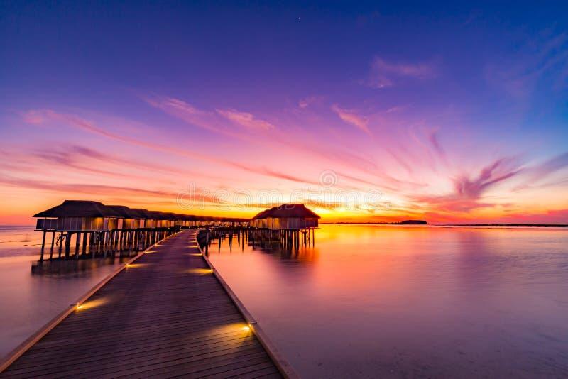 Zmierzch na Maldives wyspie, luksus wodne wille ucieka się i drewniany molo Piękny niebo, chmury i plażowy tło dla lata va obraz royalty free