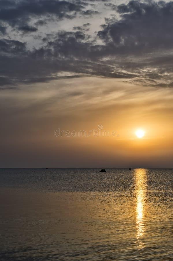 Zmierzch na morzu słoneczna ścieżka ludzie w łodzi na obraz royalty free