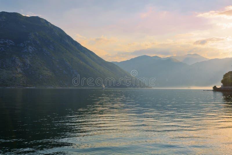 Zmierzch na morzu z mgłowymi górami fotografia royalty free
