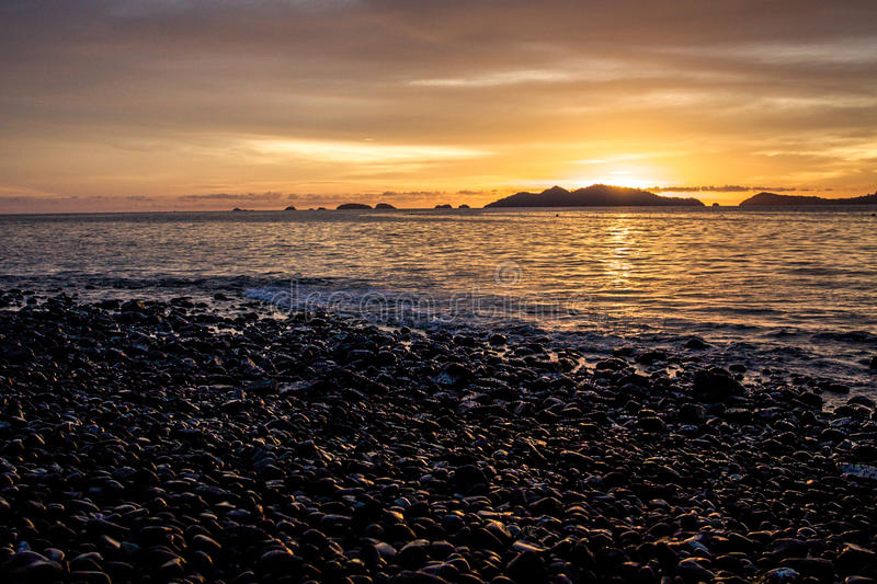 Zmierzch na otoczak plaży fotografia stock
