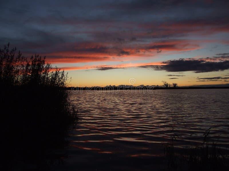 Zmierzch na płosze w tło odległym brzeg i jeziorze obraz royalty free