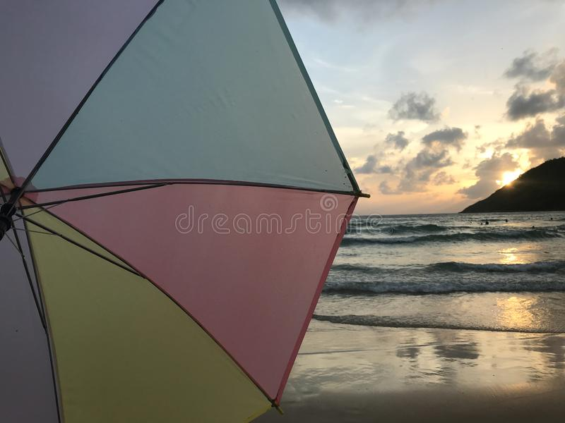 Zmierzch na plaży z pastelowym kolorowym parasolem i pięknym światłem słonecznym zdjęcie royalty free
