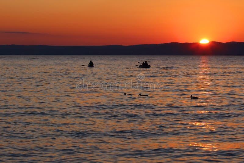 Zmierzch nad jeziorem z łodziami i kaczkami obrazy stock