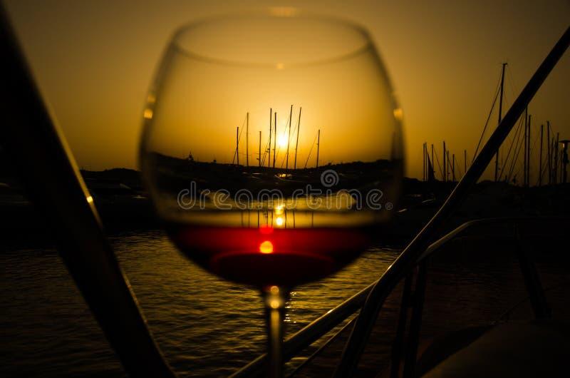 Zmierzch nad marina z świetnym szkłem wino zdjęcie royalty free