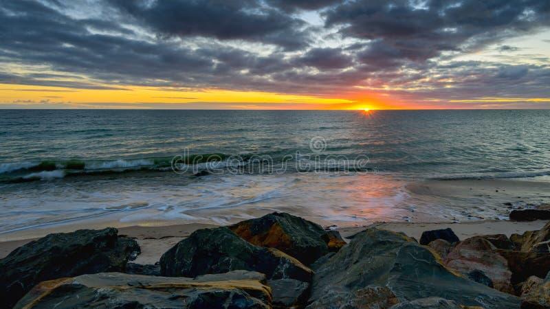 Zmierzch nad morze na skalistej plaży zdjęcie royalty free