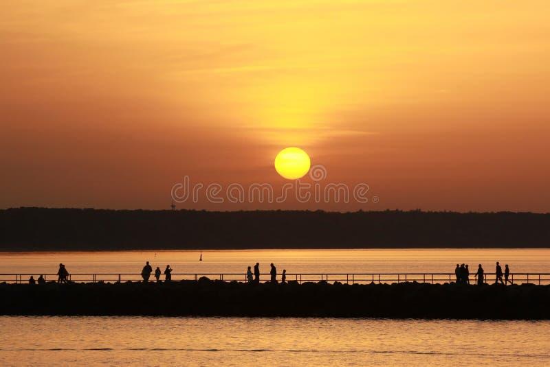 Zmierzch nad morzem, pomarańczowym niebem i ludźmi nad paradą, zdjęcia stock