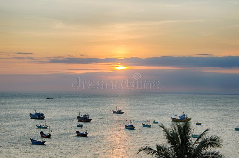 Zmierzch nad morzem słońce błyszczy między chmurami, łodzie rybackie jest widoczny morze zdjęcia stock