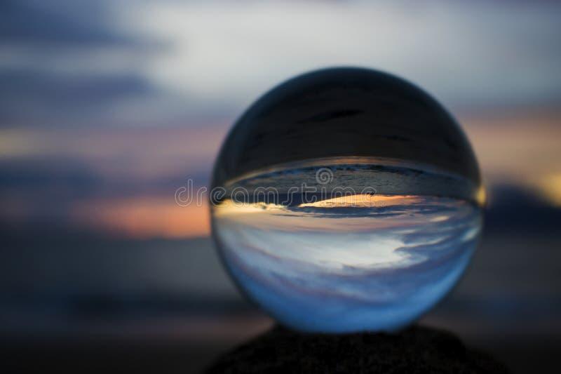 Zmierzch nad oceanem z wyspą w sylwetce w Szklanej piłce zdjęcia royalty free