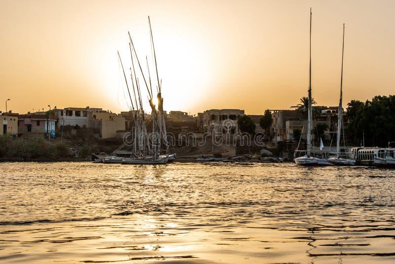 Zmierzch Nil Aswan Zachodni bank z małą wioską mieści z połowu żeglowania łodzi felucca fotografia stock