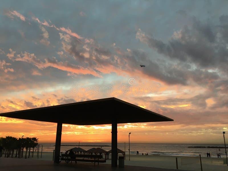 Zmierzch, piękni nieba morza plaży parasoli ludzie obraz stock