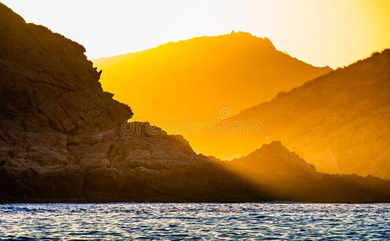 Zmierzch przed wschód słońca na oceanu wybrzeża sylwetki i oceanu górach Krajobraz przy mg?owym rankiem zdjęcia stock