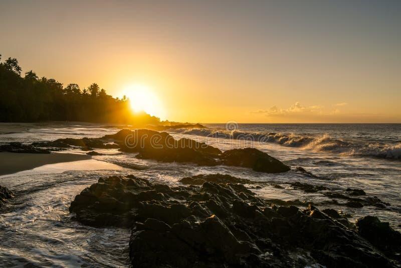 Zmierzch przy czerni skały plażą Trinidad i Tobago obraz stock