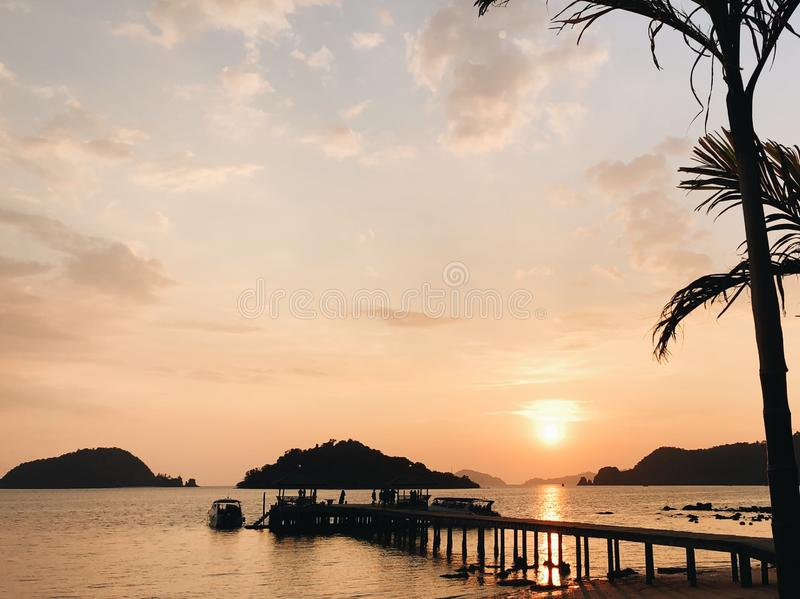 Zmierzch przy morzem, molo z łodzią przy tropikalnym wakacje obraz royalty free