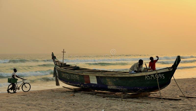 Zmierzch przy plażą w z kości słoniowej wybrzeżu z drewnianą łodzią na piasku i chłopiec odprowadzeniu z jego cyklem obrazy stock