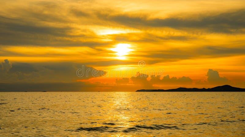 Zmierzch z światłem słonecznym nad morzem lub oceanem z światłem pomarańczowym lub złotym obraz royalty free