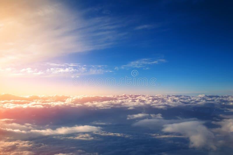 Zmierzch z jaskrawymi słońce promieniami nad cumulus chmur widokiem od okno samolot obraz royalty free