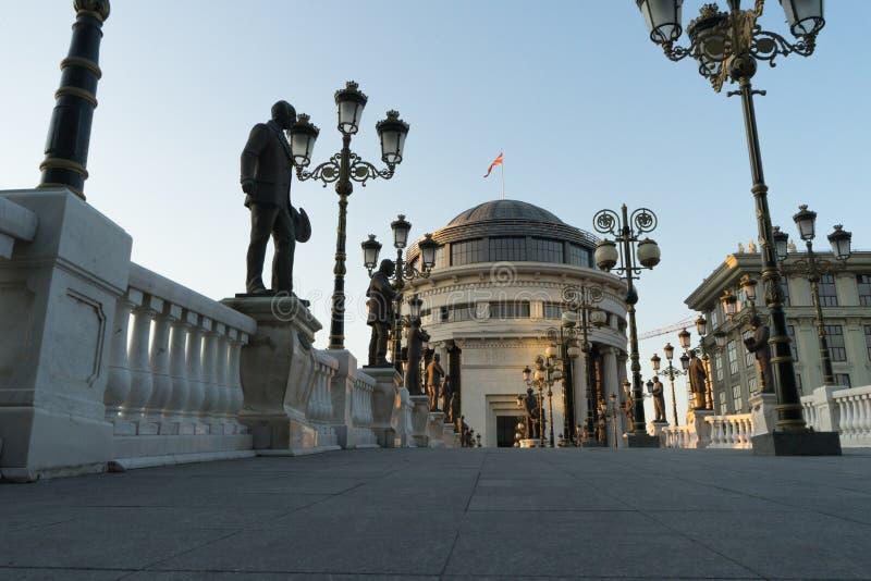 Zmierzchu czas z rzeźbami w sztuka moście przy Skopje, kapitał Północny Macedonia Rocznik lampy w ulicznym i dużym budynku z fotografia royalty free