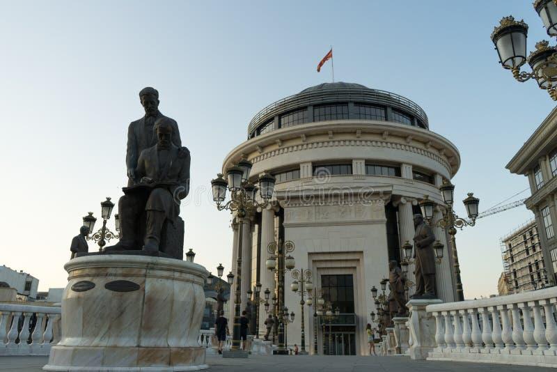 Zmierzchu czas z rzeźbami w sztuka moście przy Skopje, kapitał Północny Macedonia Rocznik lampy w ulicznym i dużym budynku z fotografia stock