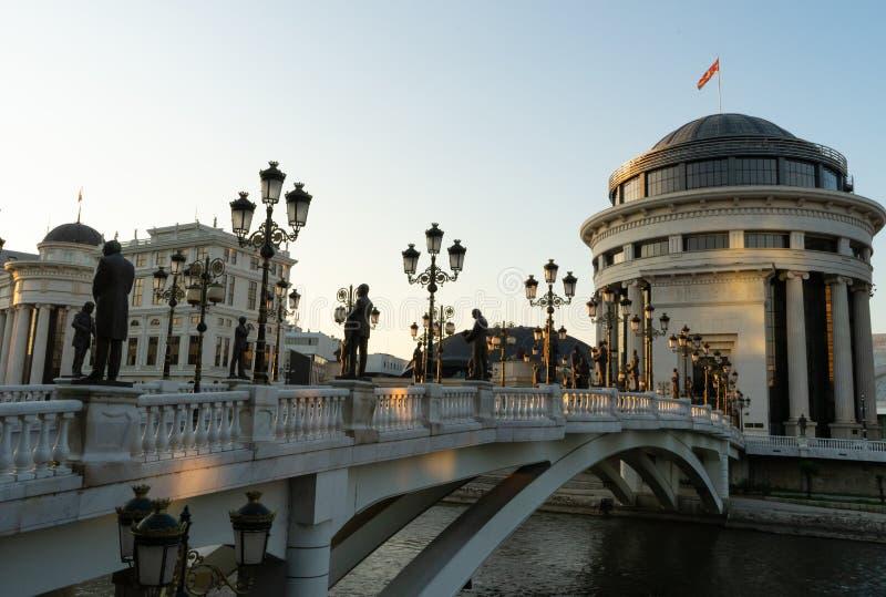 Zmierzchu czas z rzeźbami w sztuka moście przy Skopje, kapitał Północny Macedonia Rocznik lampy w ulicznym i dużym budynku z obrazy royalty free