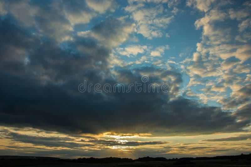 Zmierzchu przebijanie przez szarego wieczór chmurnieje w niebieskim niebie zdjęcia stock