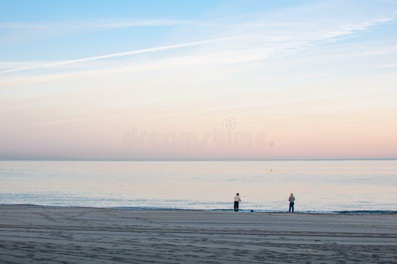 Zmierzchu widok plaża z dwa rybakami fotografia royalty free