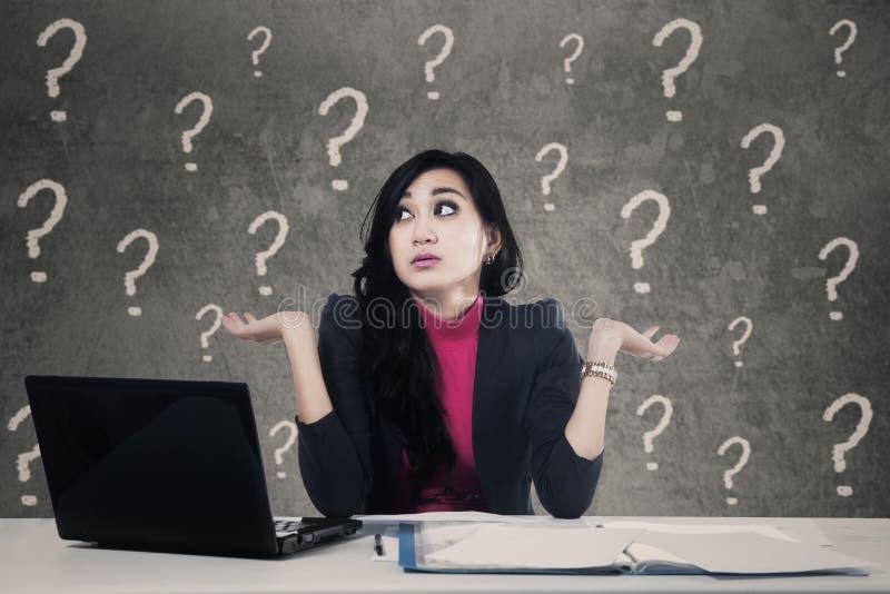 Zmieszana kobieta z znakami zapytania w biurze fotografia royalty free