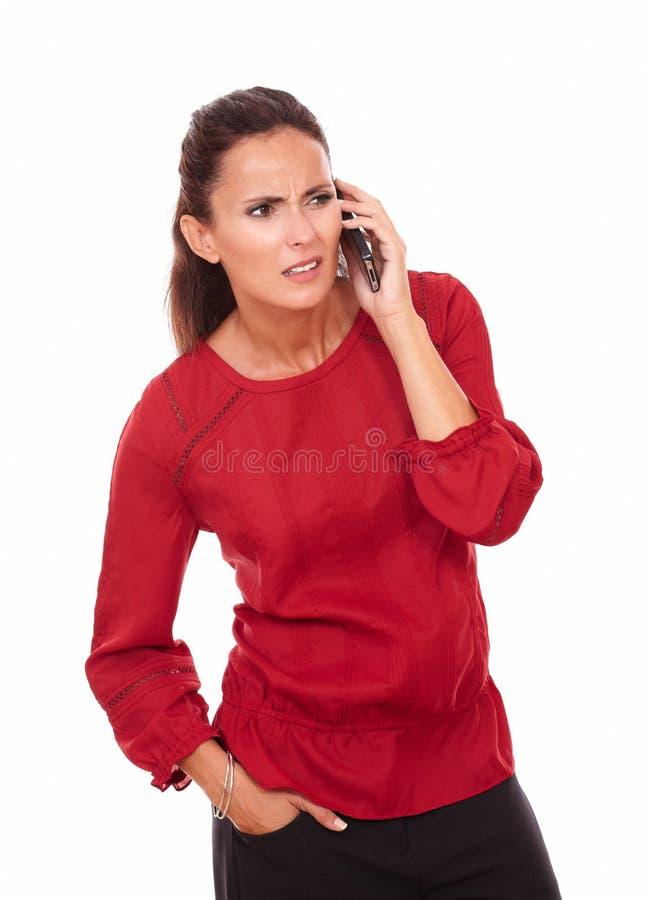 Zmieszana latynoska dama opowiada na jej telefonie zdjęcia royalty free