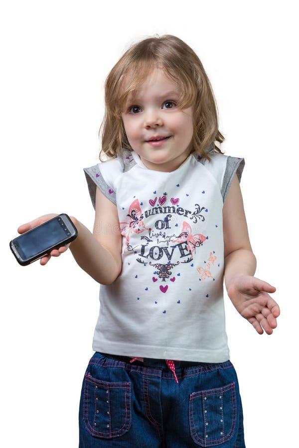 Zmieszana mała dziewczynka z telefonem w ręce obrazy royalty free