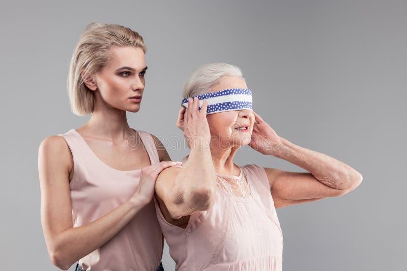 Zmieszana starsza dama zdejmuje kawałek tkanina podczas gdy poważna niemiła dziewczyna fotografia stock