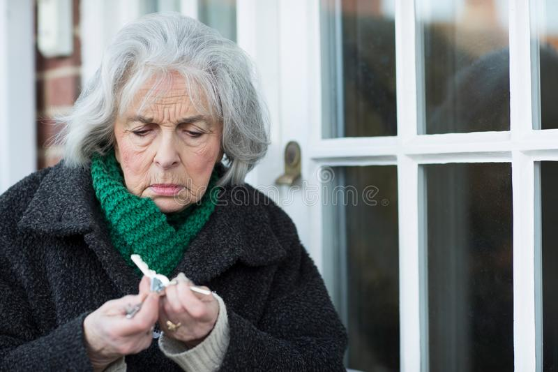 Zmieszana Starsza kobieta Próbuje Znajdować drzwi klucz obraz royalty free