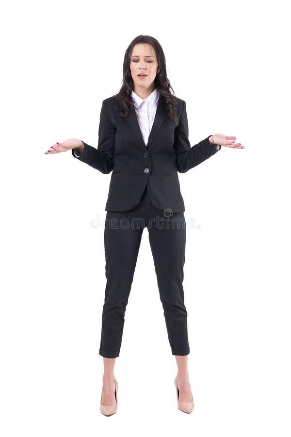 Zmieszana wzburzona biznesowa kobieta wzrusza ramionami z rękami podnosić i zamykającymi oczami zdjęcia stock
