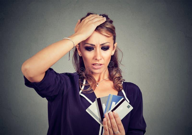 Zmieszana zaakcentowana młoda kobieta patrzeje zbyt wiele kredytowe karty obrazy stock