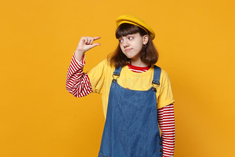 Zmieszany dziewczyna nastolatek w francuskim berecie, drelichowi sundress gestykuluje demonstrujący rozmiar z workspace odizolowy obrazy royalty free