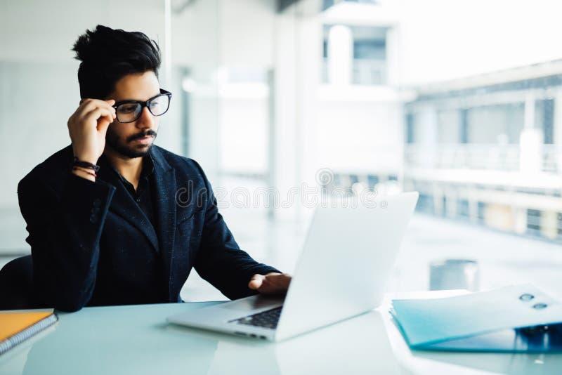 Zmieszany indyjski biznesmen pracuje na laptopie w biurze Młody indyjski mężczyzna myśleć nad projektem przy jego biurkiem z lapt zdjęcia stock