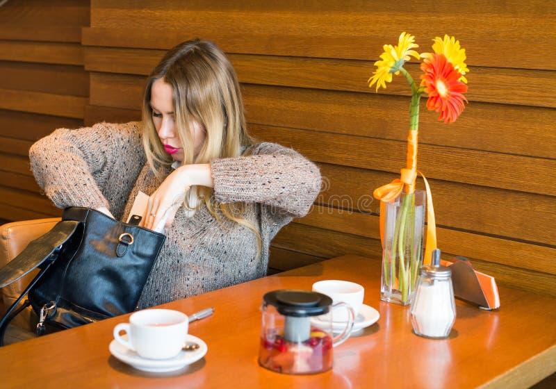 Zmieszany kobiety gmeranie coś w jej torbie obrazy stock