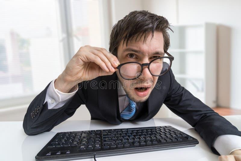 Zmieszany lub niepewny mężczyzna jest pracujący z komputerowym ciebie i patrzeć obraz royalty free